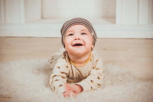 A smiley baby on a rug.