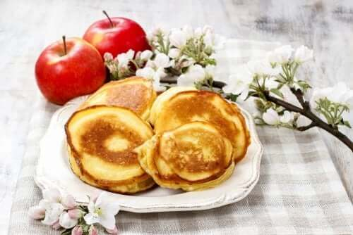 A still life of pancakes, apples and chestnut flowers.