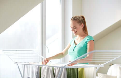 A woman hanging clothes on a drying rack.