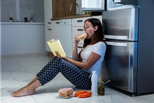 A woman reading and eating by the fridge.