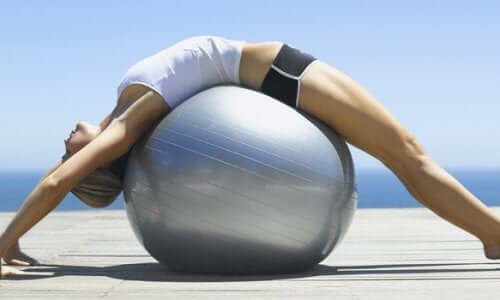 A woman stretching over a yoga ball.