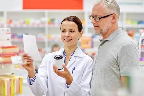 A pharmacist filling a man's prescription.