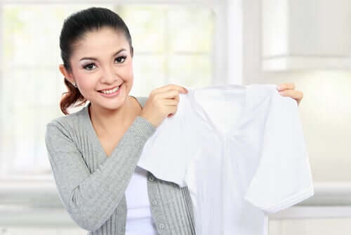 A woman removing stains from a white shirt.