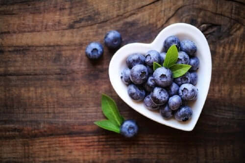 A heart-shaped bowl with blueberries.
