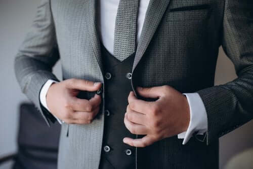 A groom buttoning up a jacket.
