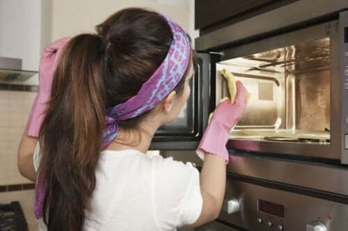A woman cleaning a microwave.