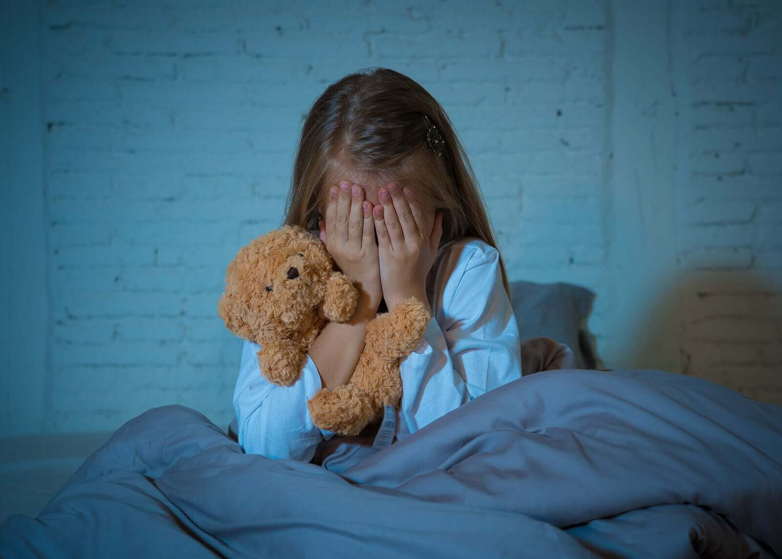 A young girl crying in her bed during the night.