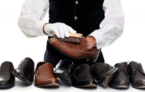 Professional cobbler with many pairs clean leather shoes