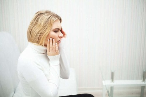 Blonde woman touching her cheek because she has a dental pain