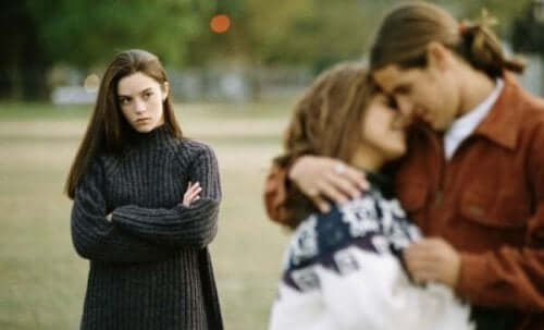 A couple in a loving embrace while a third person watches resentfully.