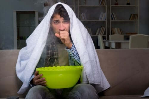 A man with a towel on his head holding a bowl.