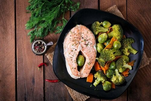 A plate of salmon, broccoli and brussel sprouts.