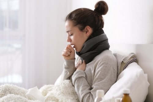 A woman in bed coughing trying to overcome a cold at home.