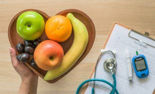 A bowl of fruits and the blood glucose meter.