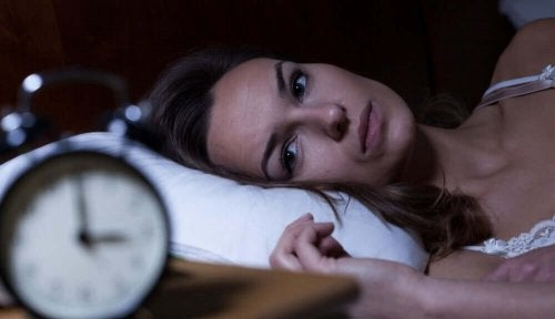 Woman laying in bed looking at clock has insomnia summertime headache