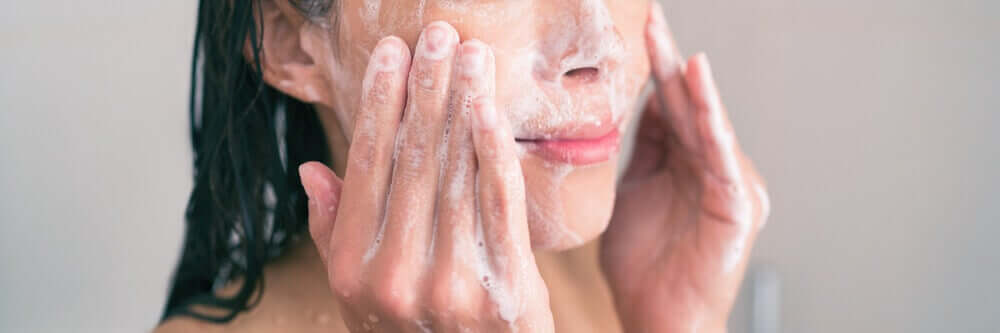A woman washing her face.