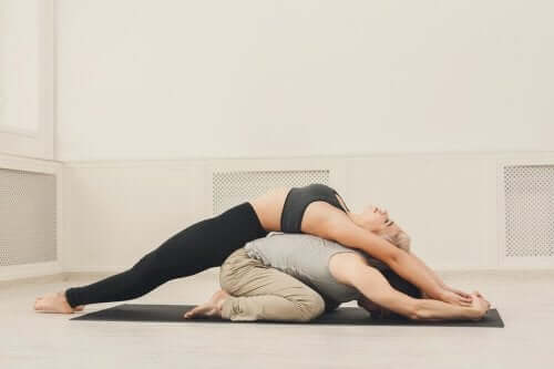 A woman stretching over a man's back.