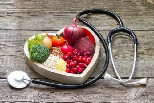 Fruits in a heart-shaped bowl and a stethoscope.