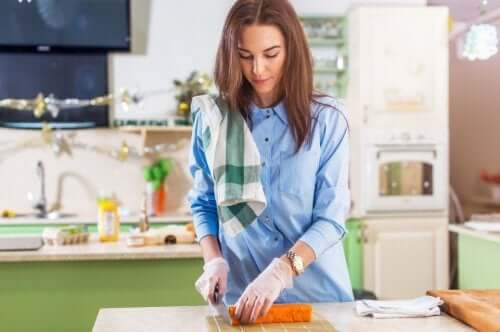 A pregnant woman cutting vegetables.