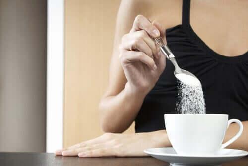 A woman adding sugar to her tea.