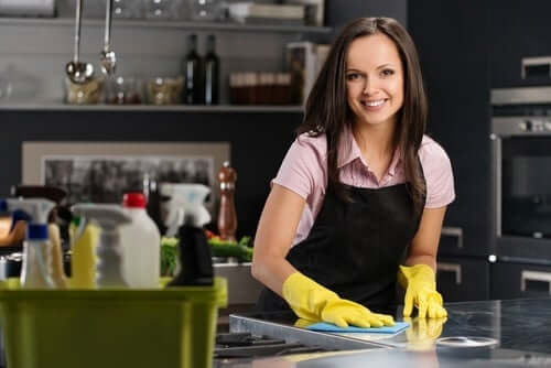 A woman cleaning her kitchen counters.