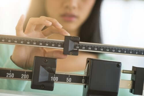 A woman weighing herself.