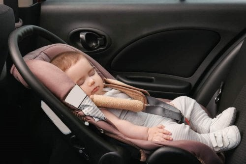 A baby sleeping in a car, unconcerned about deformational plagiocephaly.