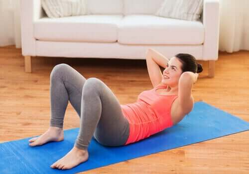 Woman doing situps in her living room on mat abdominals
