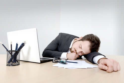 A man who fell asleep in front of his desk.