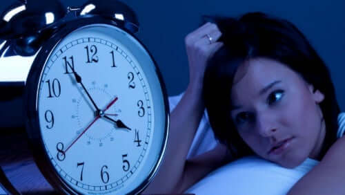 A woman staring at her clock, unable to sleep.