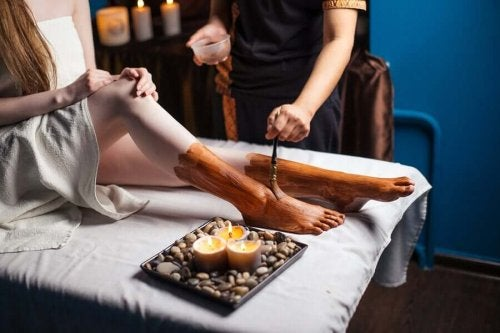 A person applying clay on someone's feet.