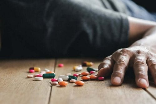 A person lying next to pills.