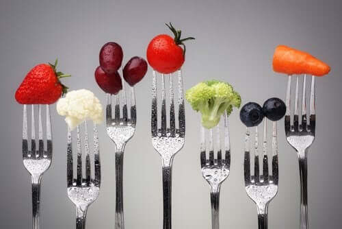 A set of forks with various types of food.