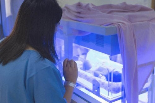 A woman looking at a baby in an incubator.