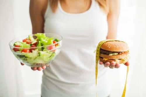 A woman with a salad and a hamburger.