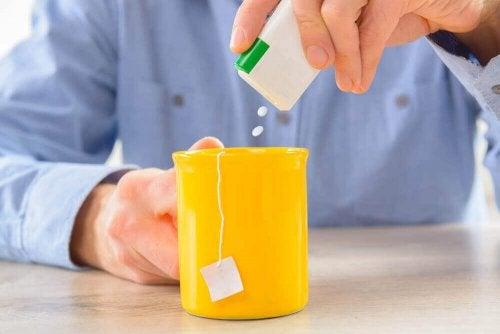 Man pouring artificial sweetener into tea diet soda.
