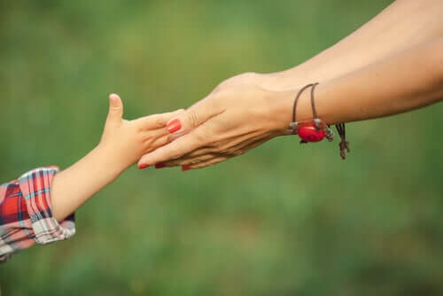 A mother holding her daughter's hand.