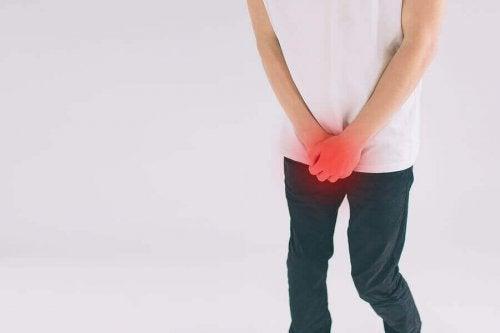 Man med smärta på grund av knölar på penis.