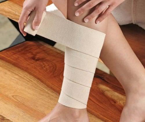 A person bandaging their leg.