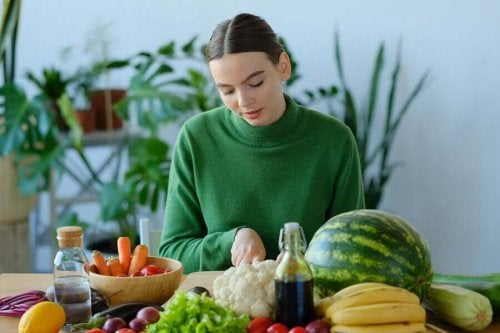 A woman surrounded by fruit and vegetables that contain vitamin A.