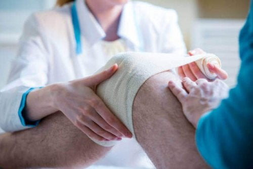 Doctors dressing a knee with a bandage.