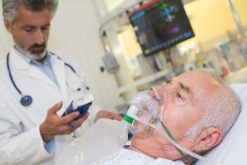 A patient getting oxygen through a mask.