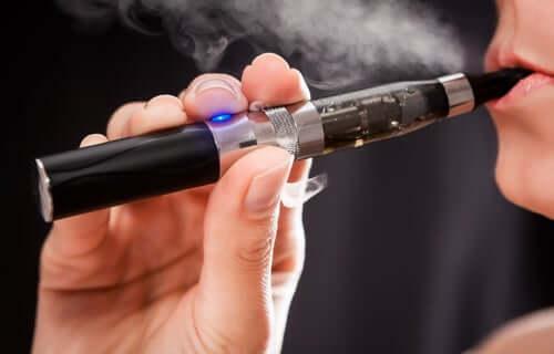 A person inhaling aerosol from a e-cigarette.