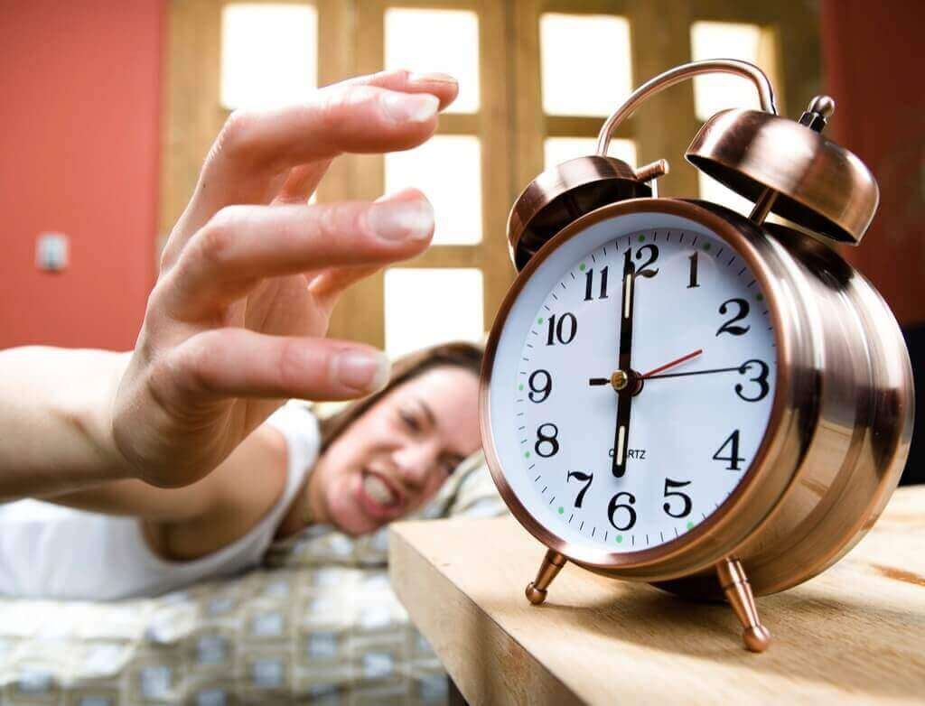A woman angrily turning off the alarm.