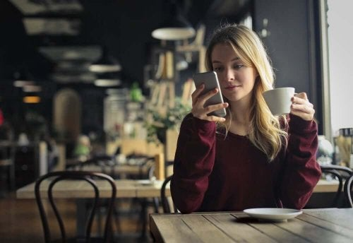 A woman drinking coffee while looking at her phone.