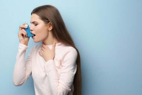 A woman using an inhaler due to an asthma attack.