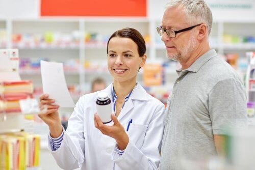 A pharmacist telling a man how to read medication package inserts.
