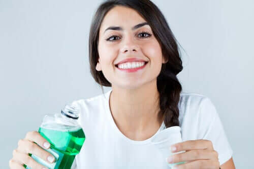 A woman pouring mouthwash in a cup.