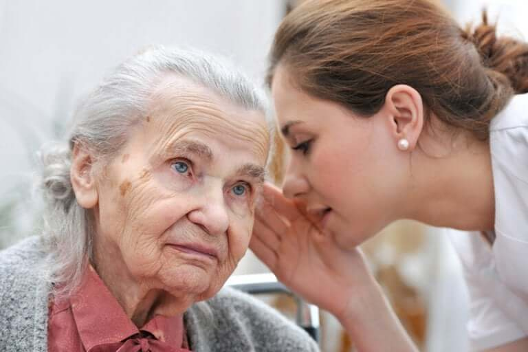 A woman speaking to an elderly lady.