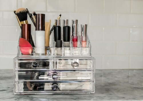 A makeup organizer with makeup and brushes.